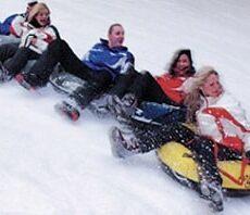 Eine Gruppe mit 5 Personen Rodel auf der Rodelbahn im Snowtropolis
